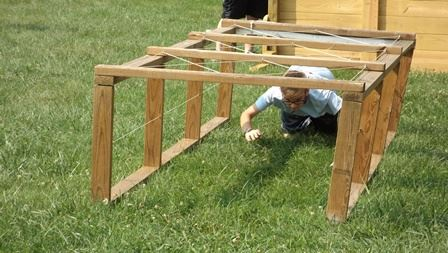 Child crawling beneath wooden structure