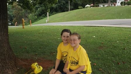 Two children in yellow shirts smiling