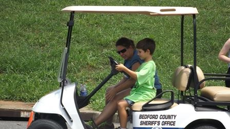 Child driving golf cart with instructor as passenger
