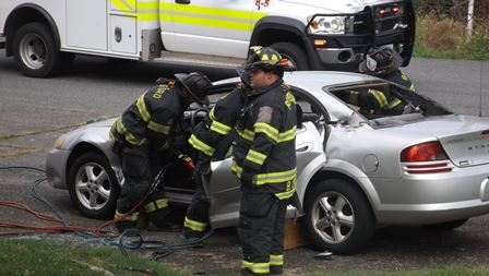 Firefighters working on a car